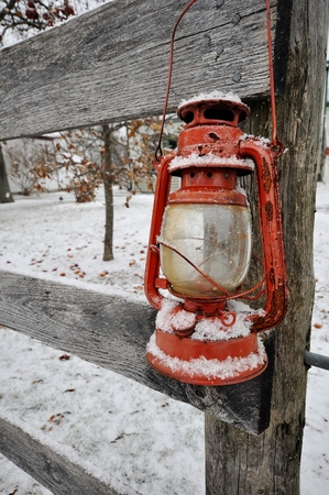 Red lantern hung on a wooden fence post covered in snow