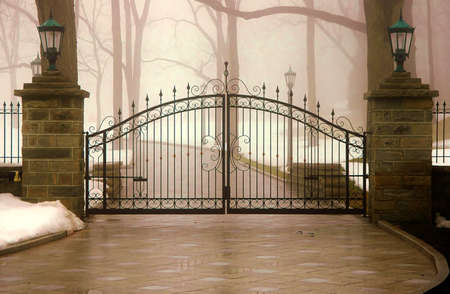 Foggy iron gated entrance way to a long driveway