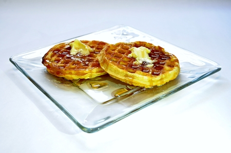Waffles with melted butter and maple syrup on glass plate