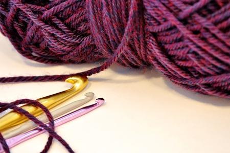 dark purple acrylic yarn with three crochet hooks isolated on white background Stock Photo