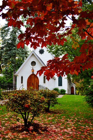 little white chapel church behind the red Autumn maple leaves