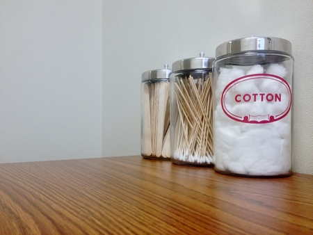 Cotton Balls, cotton swabs and tongue depressors in canisters on a desk in the doctors office