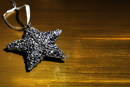 Silver Christmas star ornament on a golden background