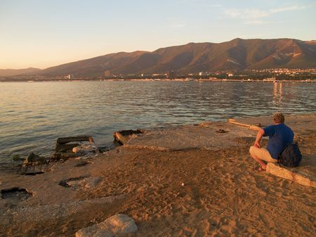 tourist sitting on a sea beach and looking on sea, mountains and town Stock Photo - 2842773