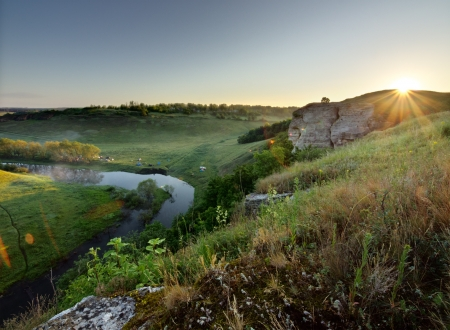 Beautiful landscape with bright sun and river in a gorge at sunrise. View from above. photo