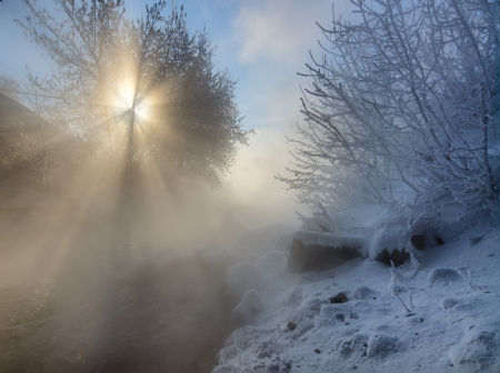 Beautiful winter landscape with visible sun-rays and frozen river photo