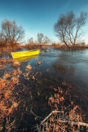 thawed: Early spring landscape with a wooden boat on a flooded river and thawed ice.