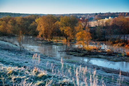 winter thaw: Cold morning landscape with a river. Grass covered by hoarfrost
