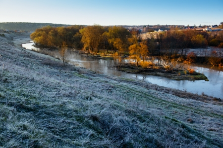 Cold morning landscape with a river. Grass covered by hoarfrost photo
