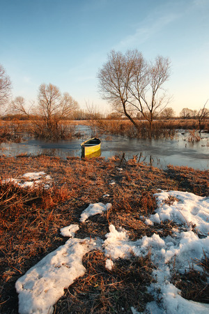 oka: Early spring landscape with a wooden boat on a flooded river and thawed ice.