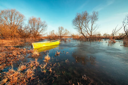 Early spring landscape with a wooden boat on a flooded river and thawed ice  photo