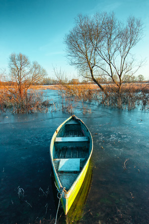thawed: Early spring landscape with a wooden boat on a flooded river and thawed ice