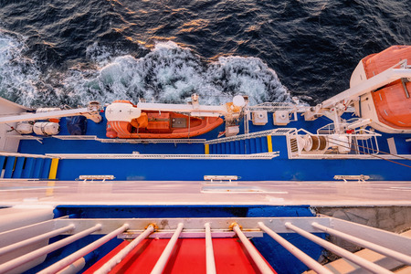 lifeboats: Board of the cargo-passenger ferry with orange lifeboats at sunset. View down from upper deck