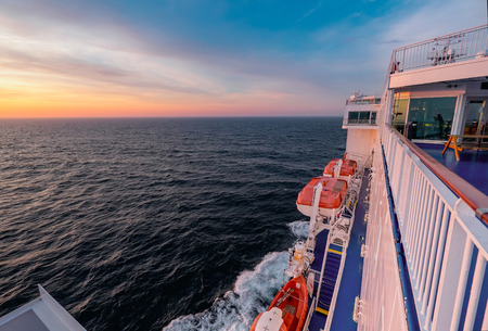 lifeboats: Board of the cargo-passenger ferry with orange lifeboats at sunset. Stock Photo