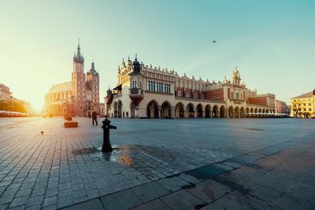 日の出クラクフのマーケット広場。Mariacki 大聖堂と織物会館。ポーランド