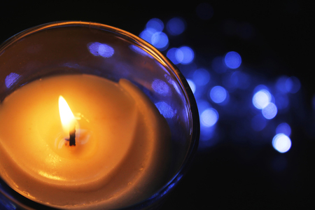semitransparent: Burning candle with christmas lights