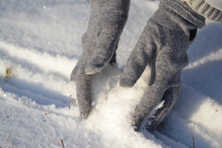 gloved: girl takes snow gloved hands