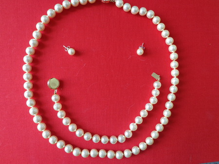 chuckle: Face of white pearls on a red