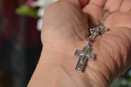 handbreadth: Orthodox cross, silver, in a female hand
