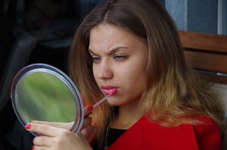 seventeen: Girl looks into the mirror and lipstick with a brush