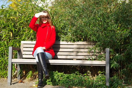 girl in red dress sitting on a bench and covers the face from the sun