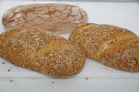 loaves: Three loaves of bread on a white table