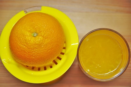 juicer: Orange on a hand juicer and a glass of juice Stock Photo