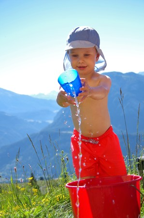 fair skinned: boy in panama shorts and pours water from a plastic cup