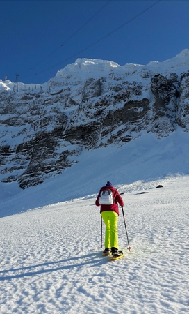 woman in a ski suit climbing a snowmobile in a mountain