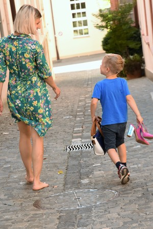 Young woman in a dress is walking with a little boy down the street