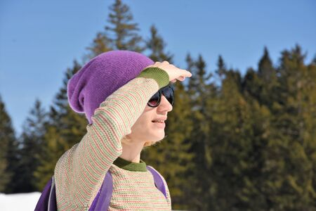 Young woman stands on a mountain looking into the distance in sunglasses Reklamní fotografie