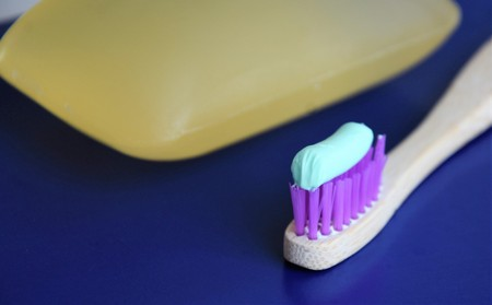 wooden toothbrush with toothpaste and soap on a blue background