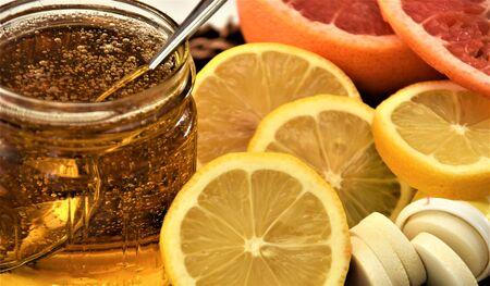 Lemons, grapefruit, a jar of honey and vitamin C tablets