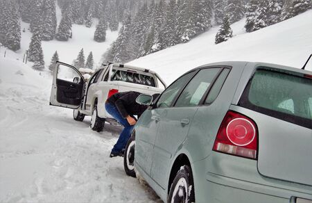 Two cars stuck in snowy mountains on a winter day