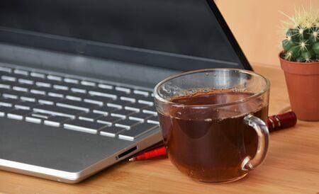 Laptop, cactus, pen and glass mug with tea