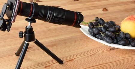 Teleobjetivo para smartphone sobre trípode con melocotones y uvas negras