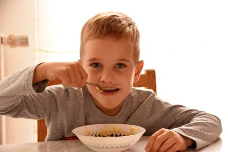 Boy sits on a chair at the table and eats pasta from a plate Reklamní fotografie