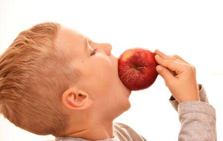 Boy in profile bites a whole red apple Reklamní fotografie