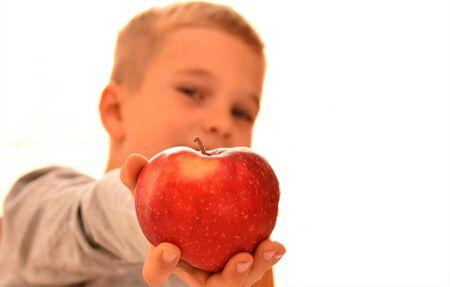 Boy with a red apple on a white background Reklamní fotografie