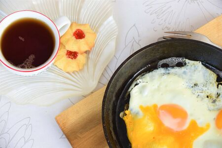 Breakfast on the table, scrambled eggs in a cast iron skillet, tea in a mug and cookies on a saucer Reklamní fotografie