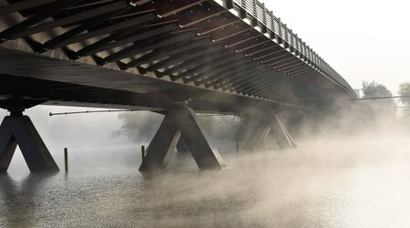 Steam from the river under the bridge in the early morning