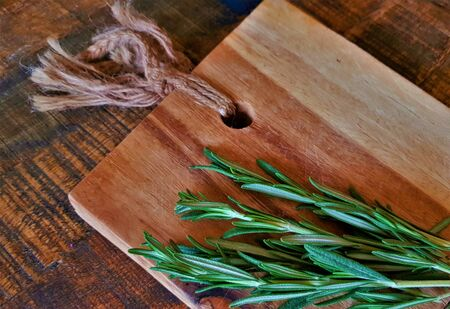 Sprigs of rosemary on a wooden natural board