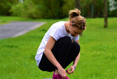 Girl sits on a cobblestone tying shoelaces on sports shoes