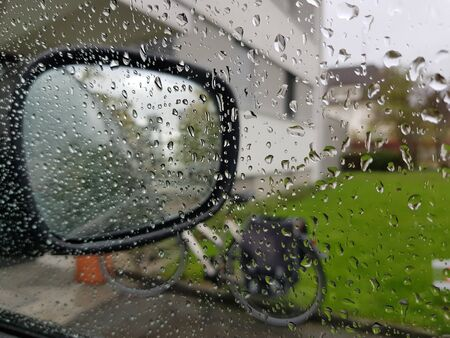 Raindrops on glass, car mirror and bicycle outdoors