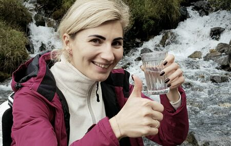 Smiling young woman standing with a glass of water in a hand near a mountain river Reklamní fotografie
