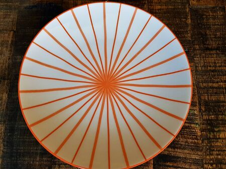 White plate with orange stripes on a wooden brown table