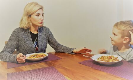 Young woman sits at table with a boy and eat pasta for lunch