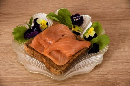Slice of bread with sturgeon fillet and salad leaves with flowers