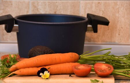 Pan with handles and vegetables on the kitchen table Reklamní fotografie