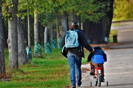Child riding a bicycle next to a walking woman